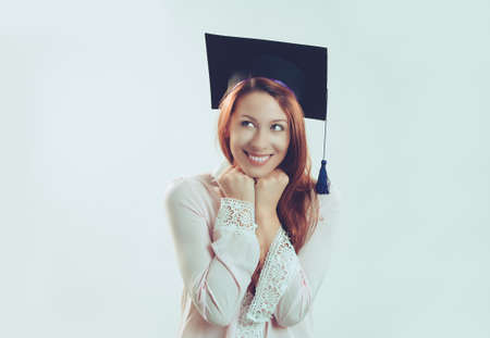 Portrait closeup young beautiful thoughtful graduate graduated student girl young woman in cap gown looking up thinking isolated light blue wall background. Graduation ceremony future career concept 免版税图像 - 151021715