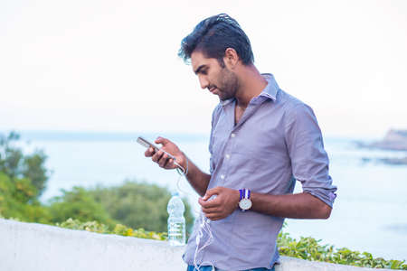 Side profile of a furious man watching apps on smart phone isolated  outdoors, on nature, sea on background