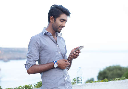 Handsome smiling businessman guy having fun listening to music or receiving good news message on phone spending time outdoors sea, sky green bushes on background. Positive face expression and emotion