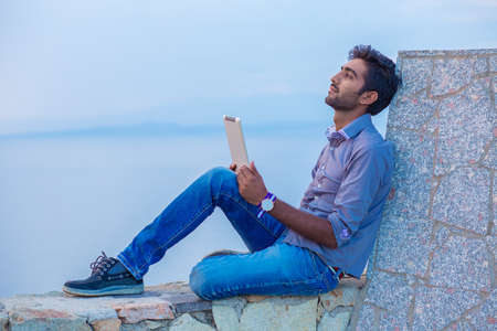 Man thinking while using pad looking to blue sky while sitting on a concrete bridge above the sea taking deep breath enjoying freedom at sunset sea on background. Melancholic thoughtful person