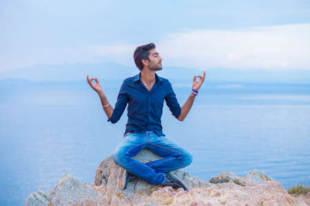 Man in yoga meditation pose sitting on a rock stone shore above the sea taking deep breath relaxing at sunset blue sky and sea on background. Find harmony and balance enjoying freedom, nature concept