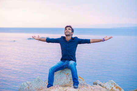 Man smiling looking up to blue sky taking deep breath celebrating freedom sea background at sunset. Positive emotion face expression feeling success peace mind concept. Free happy guy enjoying nature