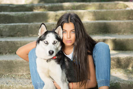 Pretty girl and her pet. Swag rapper woman with her husky dog isolated urban grey wall background sitting on stairs both looking at you camera. Taking dog out. The man's women best friend concept Banque d'images