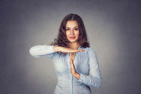Closeup portrait, young, happy, smiling woman showing time out gesture with hands isolated on gray wall background. Positive human emotion facial expressions, feeling body language reaction, attitude