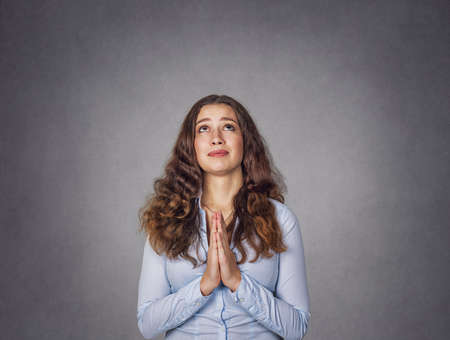 Closeup portrait of a young woman praying isolated on studio gray background. Model girl with long wavy curly hair in blue formal shirt. Closeup portrait. Positive human emotion, face expression, body language.