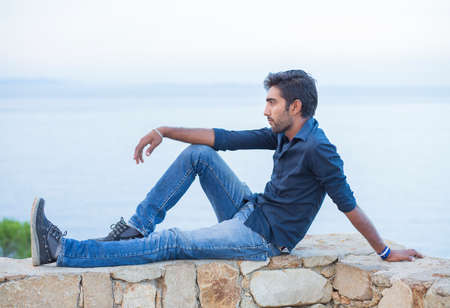 Man thinking looking to blue sky while sitting on a concrete bridge above the sea taking deep breath enjoying freedom at sunset sea on background. Melancholic thoughtful person, peace mind concept. 写真素材