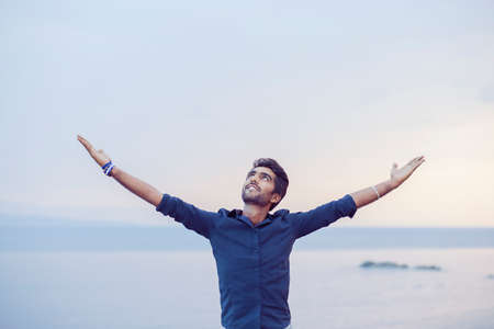 Man smiling looking up to blue sky taking deep breath celebrating freedom sea background at sunset. Positive emotion face expression feeling success peace mind concept. Free happy guy enjoying nature Фото со стока
