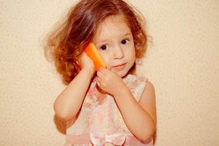 Portrait of cute little girl with cell phone isolated on pastel brown wall background