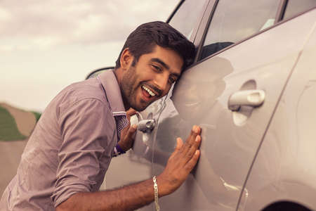 Young hispanic man wearing in formal shirt holding is petting his car and smiling outdoors. A new car, new driver concept 版權商用圖片