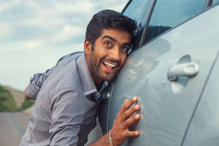 Happy Indian guy, man in formal business shirt petting his new car, listening to his motor sound happy about it outdoors on a urban road.