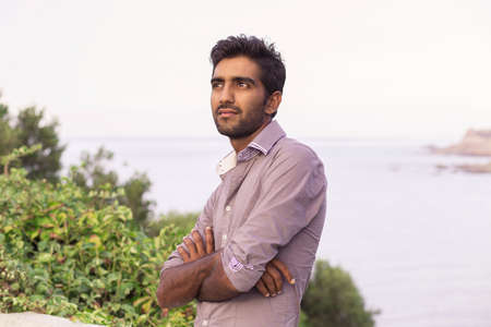 Portrait of elegant Indian man in formal shirt outdoors, near the lake sea with lots of copy space