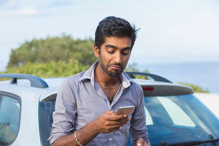 Indian skeptical frustrated surprised sad man checking looking at phone texting, calling dealership after a car breakdown