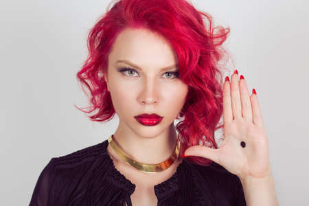 Woman with black dot on her palm give signal about domestic violence. Red head curly bob hairstyle girl isolated light gray grey white background. Mixed race latin hispanic caucasian fashion model
