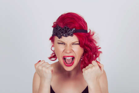 Portrait angry young woman screaming fists clenched. Red head curly bob hairstyle girl isolated light gray grey white background. Mixed race latin hispanic caucasian fashion model