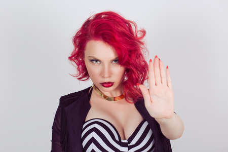 Woman making stop it, no stay there with hand gesture. Red head curly bob hairstyle girl isolated light gray grey white background. Mixed race latin hispanic caucasian fashion mode