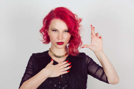 A liar. Woman sly witness making a false promise or testifies falsely hands gesture. Red head curly bob hairstyle girl isolated light gray white background. Mixed race hispanic caucasian fashion model