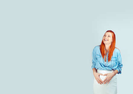 Wonderful young woman with ginger hair holding hands in heart of shape on pregnant belly smiling laughing happily looking up cheerful isolated on light blue background. 版權商用圖片