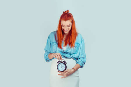 Happy woman smiling holding a clock at big pregnant belly showing that her biological watch is ticking and she is expecting a baby isolated on light blue background. It is time to be a mother concept.