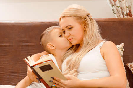 Beautiful woman sitting with boy on bed and reading book while cuddling gently and spending time together