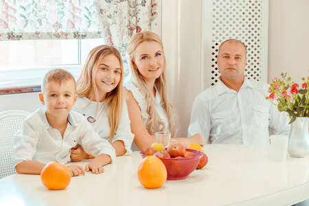 Adult man and woman with teen girl and little boy all wearing white and sitting at table with fruit looking at camera