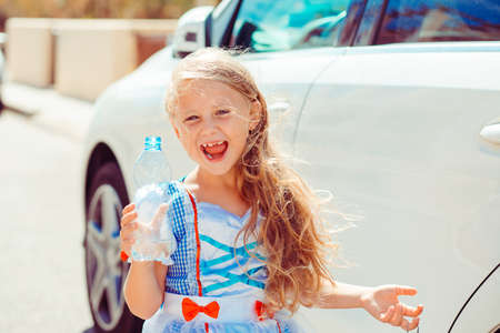 Grimacing funny girl in adorable dress holding bottle of water and looking happily at camera outside in sunlight 版權商用圖片