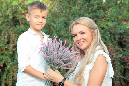 Adorable boy giving bouquet of beautiful flowers to charming woman standing in green garden and smiling at camera 版權商用圖片
