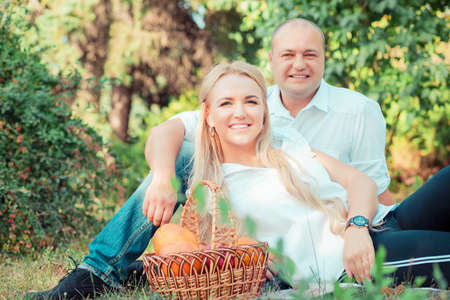 Excited adult man and woman embracing and looking at camera while sitting on green grass in park having fruit picnic 版權商用圖片