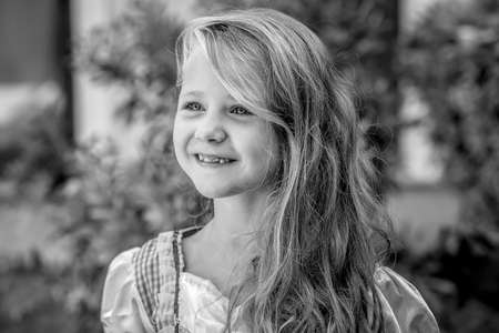 Black and white shot of wonderful little girl with long curly hair smiling happily while looking away 版權商用圖片