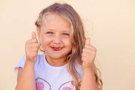 Adorable little girl with mouth all in chocolate smiling at camera and thumbs