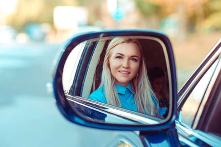 Reflection in side car mirror of adult beautiful woman in blue shirt sitting inside and looking at camera