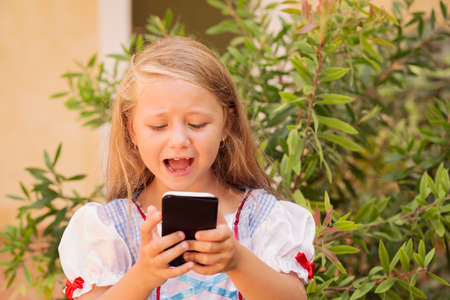 Little girl in wonderful dress using smartphone and crying emotionally looking upset outside against green 版權商用圖片