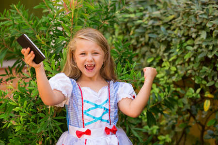 Cheerful little girl in dress holding smartphone and screaming with excitement at camera celebrating success