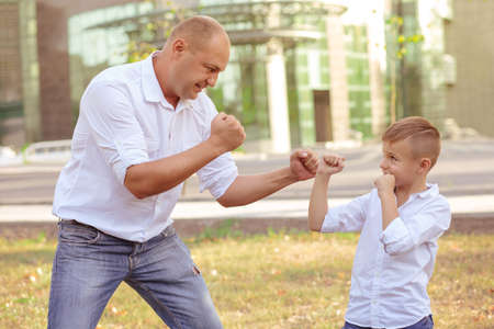 Adult man and kid both in denim and white shirt showing mock fight having fun in summer park