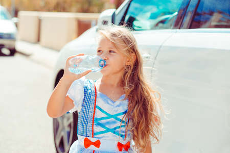 Little charming girl wearing pretty dress and standing on street drinking refreshing water from plastic bottle