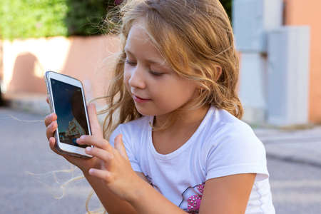 Little girl using smartphone camera and tapping on screen while relaxing outside in summertime 版權商用圖片