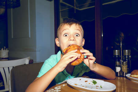 Adorable playful boy making face while biting delicious pie having meal in restaurant and looking at camera