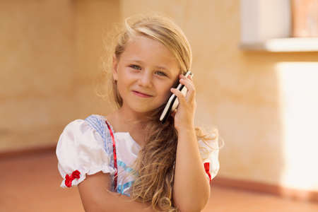 Pretty little girl with long fair hair and in dress using smartphone and making call while smiling at camera 版權商用圖片