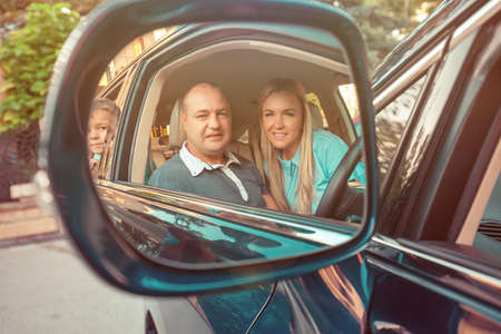 Adult man and woman sitting inside of car with kid on backseat all looking at camera through reflection in mirror
