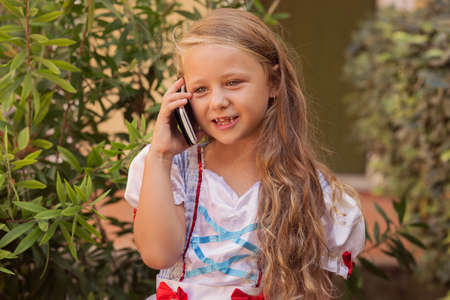 Adorable girl in princess dress and with long curly hair using smartphone and speaking on street in summertime 版權商用圖片