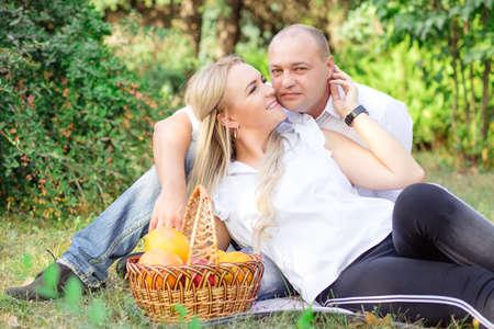 Cheerful adult man and woman cuddling on green grass with bucket of fruit near having romantic picnic 版權商用圖片