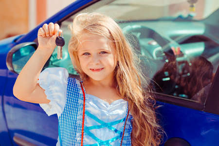 Pretty girl with long golden hair wearing princess dress and showing keys standing near new blue car in sunlight