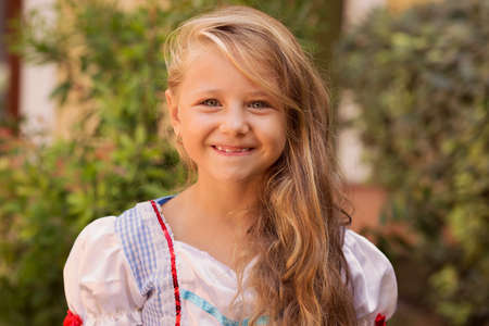Adorable little girl with long golden hair wearing dress and smiling at camera on green nature background