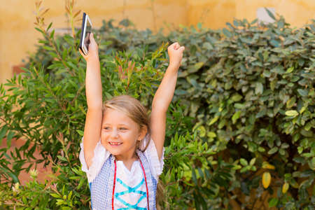 Wonderful little girl holding hands with smartphone up and looking super happy with victory on green bushes