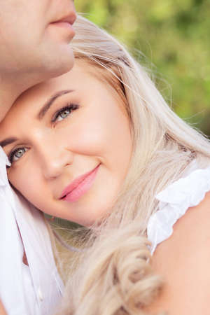 Close-up of beautiful happy woman with blond hair cuddling with adult man looking at camera