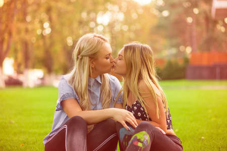 Woman and teen daughter giving kiss to each other while cuddling on green summer lawn in park