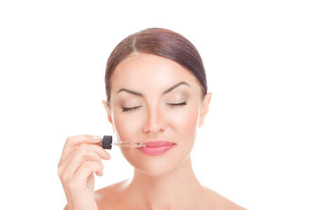 Lip vitamin Serum For woman. Young girl applying serum essence essential oils to her lips for moisture solution eyes closed isolated on white background Positive face expression mixed race latina girl
