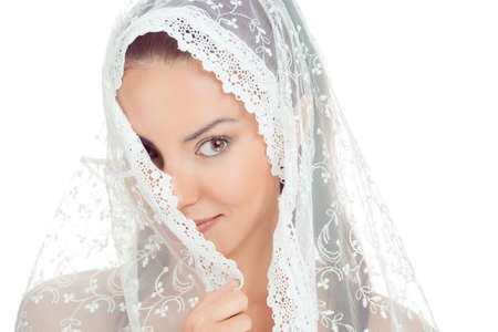 Beautiful shy bride covering face with fashion wedding style - on white background. Closeup portrait of young gorgeous bride. Wedding. Studio shot. Woman in white  portrait with veil over her face