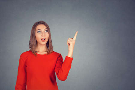 Surprised woman with open mouth pointing to the copyspace isolated on gray studio wall background. Attractive girl in casual clothes pointing her finger up. Business lady in red dress, bob hairstyle.