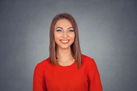 Portrait of a beautiful woman smiling looking at camera. Business woman in red dress, bob hairstyle. Isolated on gray grey studio wall Background. Positive face expression, human emotion body language