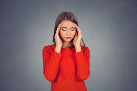 Portrait stressed out young woman with worried face expression hands on her head looking down. Business woman in red dress, bob hairstyle. Isolated on gray grey studio wall Background. Negative face.